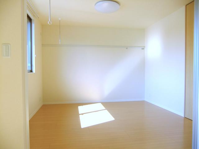 リビング脇のお部屋です。南窓の前・天井から、物干し竿を掛けられる室内干し用のリングが降りています。お洗濯がない時でもインテリアの邪魔にならない自然なデザイン。